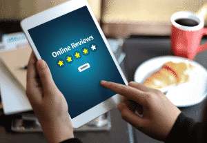 man holding white tablet with Online Reviews, four of five stars and a submit button on screen