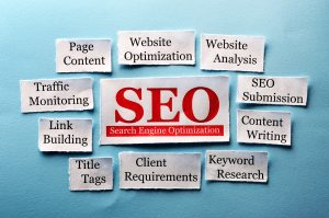 scraps of rectangular paper with SEO in red in the middle, and different types of SEO methods surrounding it
