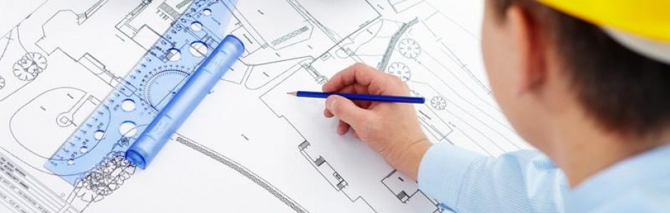 man in yellow construction helmet writing on architectural blue prints